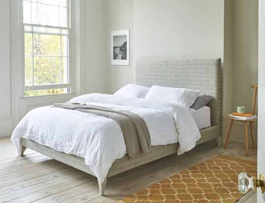 bed in neutral fabric in bedroom